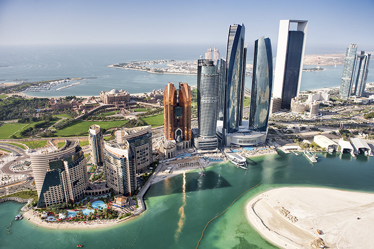 Part of Abu Dhabi, UAE with tall buildings and surrounding area viewed from the helicopter. Many details are visible in the image.